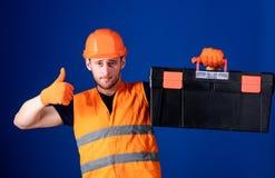 Le travailleur, réparateur, le dépanneur, constructeur sur le visage sûr porte la boîte à outils sur l'épaule Réparez le concept  Image libre de droits