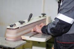 Le travailleur rectifie la partie sur la machine de meulage vue de côté sous un angle photos libres de droits
