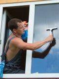 Le travailleur s'est penché la fenêtre pour la laver Image libre de droits