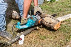 Le travailleur scie le rondin avec une scie électrique Images libres de droits