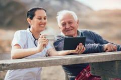 Le travailleur social de sourire soignent et patient supérieur handicapé à l'aide du comprimé numérique Photographie stock libre de droits