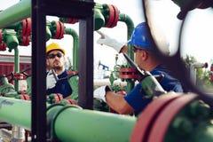 Le travailleur sur la pompe à huile regarde l'ordinateur portable et parler dans une station de radio photo stock