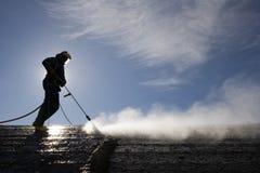 Le travailleur sur le hall d'usine nettoie le ciment Photo libre de droits