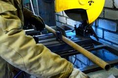 Le travailleur tient des mains le tuyau de metall pour le couper sur la machine Dans la perspective des briques blanches Photos stock