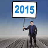Le travailleur tient le numéro 2015 sur le plancher en bois Image libre de droits
