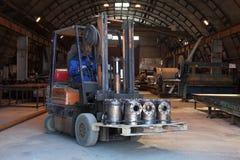 Le travailleur transporte des pièces en métal par le territoire de l'usine utilisant f Images libres de droits
