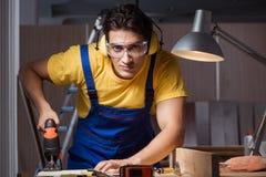 Le travailleur travaillant dans l'atelier de réparation dans le concept de travail du bois photographie stock libre de droits
