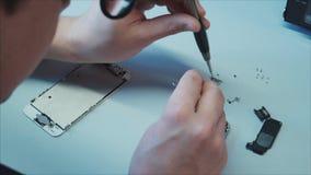Le travailleur utilise les écrans de agrandissement et les outils spéciaux à retirer un composant clips vidéos