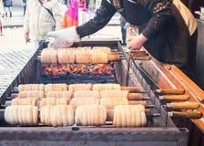 Le trdlo appelé par nourriture nationale tchèque de rue d'hiver (trdelnic) est fait cuire dans la place de Prague image stock