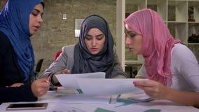 Le tre femmine arabe splendide stanno sedendo insieme tutti al desktop comune e stanno discutendo le note e stanno parlando dell' archivi video