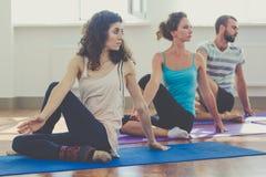 Le tre persone allegre stanno facendo l'yoga all'interno Immagine Stock