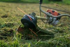 Le trimmer après travail se trouve sur l'herbe Photographie stock libre de droits