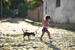 Le Trinidad, Cuba, le 16 août 2018 : Peu fille jouant avec son chien sur la rue du Trinidad images stock