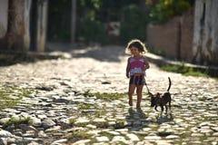 Le Trinidad, Cuba, le 16 août 2018 : Peu fille jouant avec son chien sur la rue du Trinidad photo libre de droits