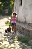 Le Trinidad, Cuba, le 16 août 2018 : Peu fille jouant avec son chien sur la rue du Trinidad image stock