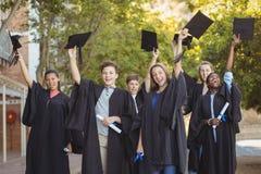 Le troisième cycle d'université badine la position avec le rouleau et la taloche de degré dans le campus Images stock
