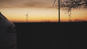 Le tronc de la voiture s'ouvre automatiquement dans la perspective du coucher du soleil et des turbines de vent banque de vidéos