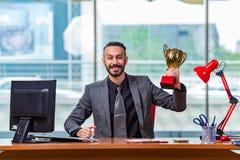 Le trophée de gain de tasse d'homme d'affaires dans le bureau Photo libre de droits