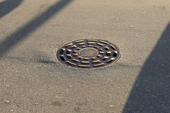 Le trou d'homme de rond de fer se trouve sur le trottoir Dans la ville, l'égout est fermé par une couverture de trou d'homme avec photos stock