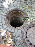 Le trou ouvert d'homme sur la rue dans le ¼ de FÃ ssen la ville Image stock