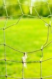Le trou sur un vieux football de porte, fond Image libre de droits
