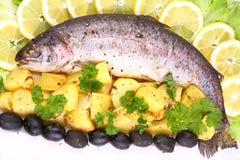 Le truite arc-en-ciel entier a grillé avec des pommes de terre, citrons Image libre de droits