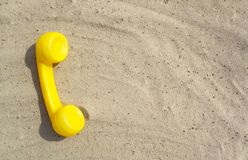 Le tube jaune d'un vieux téléphone de cru est à plat sur le sable avec un espace de copie pour votre texte avec des contacts photographie stock