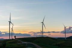 Le turbine dei generatori eolici della siluetta sull'estate del tramonto abbelliscono la i Fotografia Stock Libera da Diritti