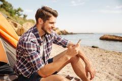 Le turisten för ung man som använder smartphonesammanträde i touristic tält Arkivbilder