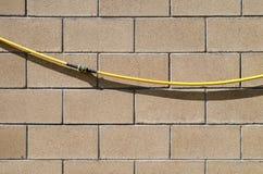 Le tuyau d'arrosage avec l'accouplement de réparation accroche sur un mur des blocs en pierre doux Fond, série de texture Image libre de droits