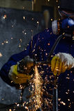 Le tuyau en métal de coupe de travailleur industriel avec beaucoup étincelle des babioles à l'arrière-plan images libres de droits