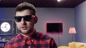 Le type actif parle à la caméra et aux points avec son doigt dans la chambre moderne banque de vidéos
