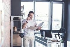 Le type adulte gai se tient dans le bureau moderne avec le smartphone Photos stock