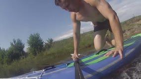 Le type apprend à se tenir sur un panneau de palette, s'exerçant sur un ressac avec un aviron, banque de vidéos