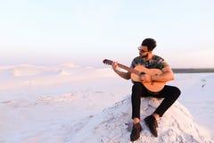 Le type Arabe attirant chante des chansons sur la guitare, se reposant sur la colline dedans Images stock