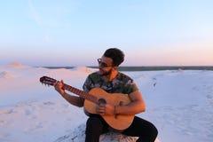 Le type Arabe attirant chante des chansons sur la guitare, se reposant sur la colline dedans Image stock