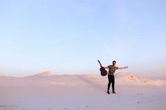 Le type arabe va inspiré par beauté de désert et joue le stri de guitare Image stock
