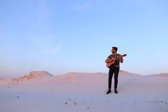 Le type arabe va inspiré par beauté de désert et joue le stri de guitare Photos stock