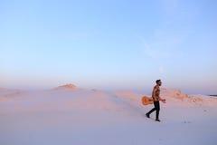 Le type arabe va inspiré par beauté de désert et joue le stri de guitare Photo stock