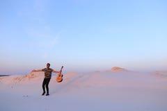 Le type arabe va inspiré par beauté de désert et joue le stri de guitare Photo libre de droits