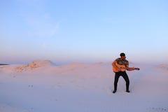 Le type arabe va inspiré par beauté de désert et joue le stri de guitare Photos libres de droits