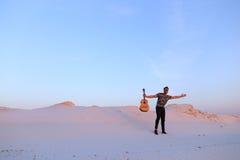 Le type arabe va inspiré par beauté de désert et joue le stri de guitare Photographie stock