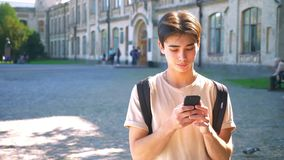 Le type asiatique heureux souriant utilise son smartphone, communication, sur la position de rue, humeur urbaine, endroit ensolei clips vidéos