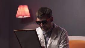 Le type attirant avec les lunettes de soleil de port de barbe et le laboratoire blanc tient l'image dans le cadre banque de vidéos