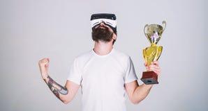 Le type avec des verres de VR a gagné le championnat, gobelet d'or disponible de prise Homme avec la barbe dans le gagnant en ver photo stock
