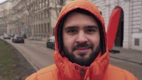 Le type avec la barbe épaisse dans les regards de capot à la caméra et aux sourires clips vidéos