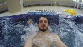 Le type avec la barbe est dans la piscine avec des bulles banque de vidéos