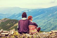 Le type avec la fille s'asseyent embrassant la haute dans les montagnes L'amour, amitié, intimité, ont plaisir à être ensemble Images libres de droits