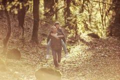 Le type avec la fille s'attaquent au coucher du soleil dans les bois, dans les montagnes Image stock