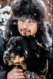 Le type avec le chien en parc en hiver snowing Photographie stock libre de droits